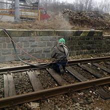 Vysokotlaké čištění kamenné zdi u kolejí